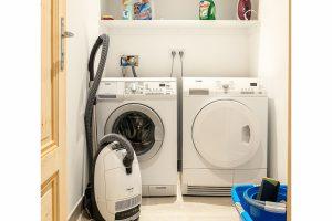 Hauswirtschaftsraum mit allen Reinigungsutensilien und hochwertiger Waschmaschine und Trockner