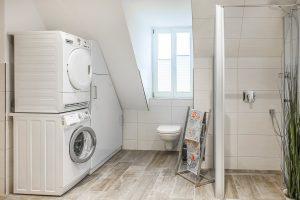 Badezimmer mit hochwertiger Waschmaschine und Trockner im Dachgeschoss
